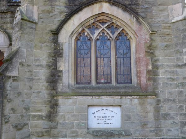 The dedication stone below the stained glass window
